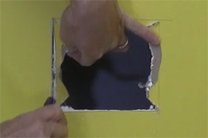 photo snapping drywall along a scored line