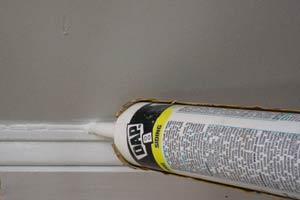 photo filling a crack along a baseboard with caulk