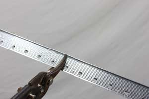 photo cutting metal drywall corner bead with tin snips