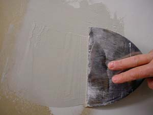 photo applying a second coat of joint compound over a patch