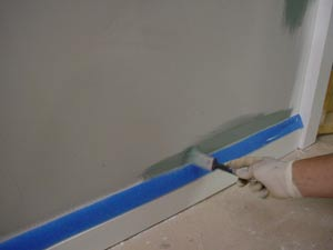 photo using a brush to paint over masking tape on a baseboard
