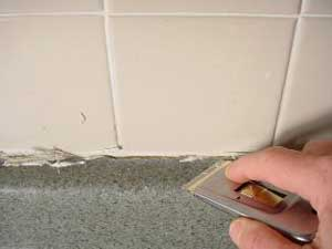 photo cutting away cracked caulk from a countertop