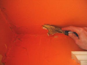 photo scraping damaged and crumbling plaster