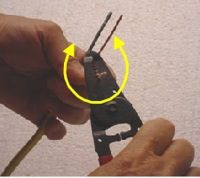 photo using wire strippers to remove electrical wire insulation