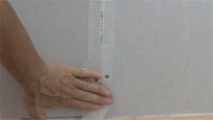 photo applying fiberglass mesh tape over a drywall butt joint