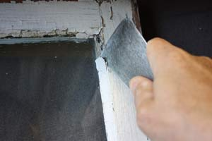 photo removing old loose glazing putty from a window sash