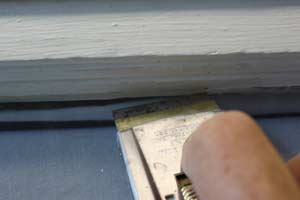 photo demonstrating how to use a razor blade to remove old paint from window glass