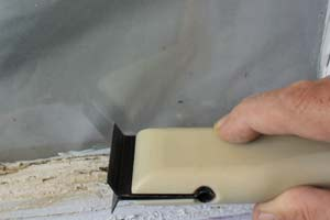 photo scraping peeling paint off a window sash