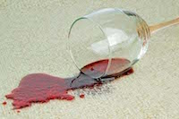 photo of a wine glass spilling wine on carpet